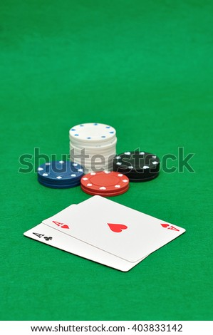 Poker chips and two playing cards displayed on a green background