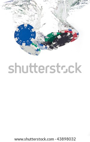 Poker chips falling into the clear water - stock photo