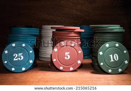 poker chips on a wooden table - stock photo