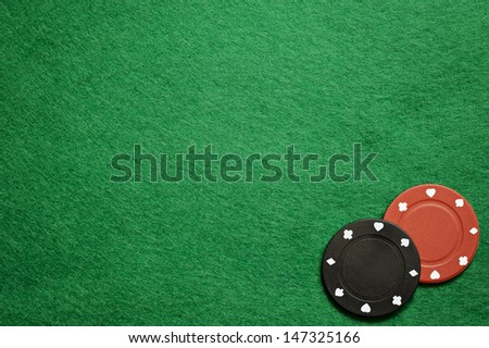 Poker chips on green cloth - stock photo