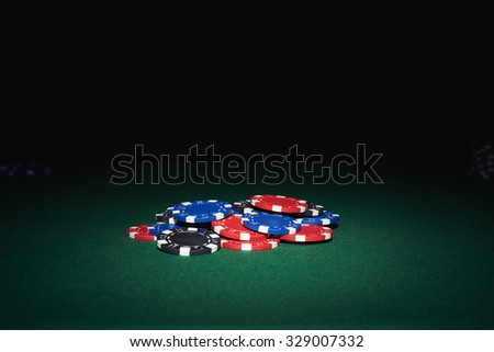 Poker chips on table in casino with black background - stock photo