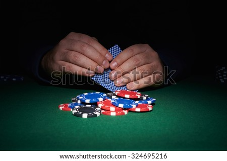 Poker chips on table with hands and cards in casino with black background - stock photo