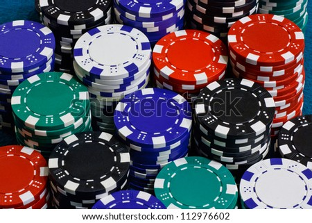 Poker chips stacked on card table - stock photo