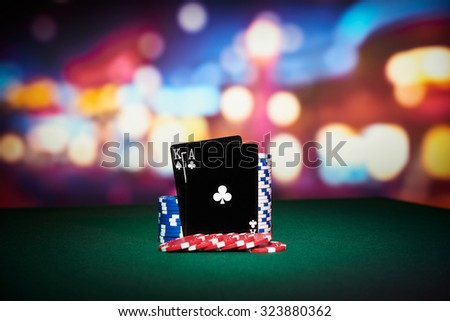 Poker chips with black cards on table in casino - stock photo