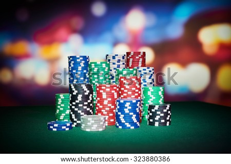 Poker chips with blur background on table in casino - stock photo
