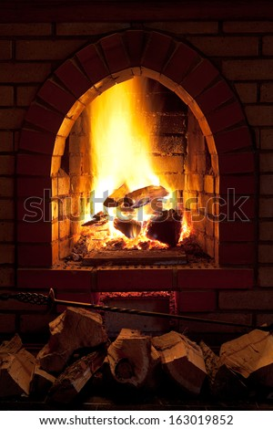 poker, firewood and of fire in home fireplace in evening time - stock photo
