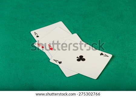 Poker four aces cards on green background