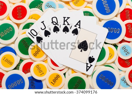 Poker hand with a straight flush in spades fanned over a colorful background of poker chips conceptual of winning at cards and gambling, overhead view