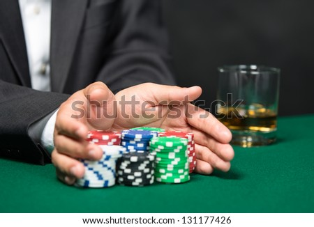 "Poker player going ""all in"" pushing his poker chips forward. Risky entertainment of gambling - stock photo"