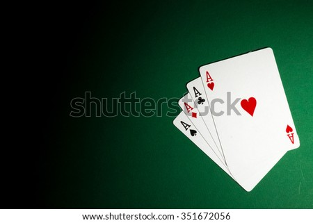 poker player holding 4 Ace of pokers beside lots of chips - stock photo