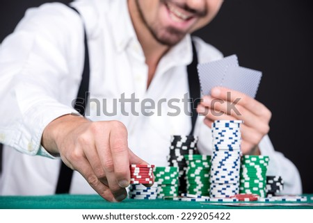 Poker player, on a black background, with poker chips on the table. - stock photo