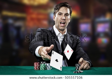 Poker player showing a pair of aces, on a casino background.