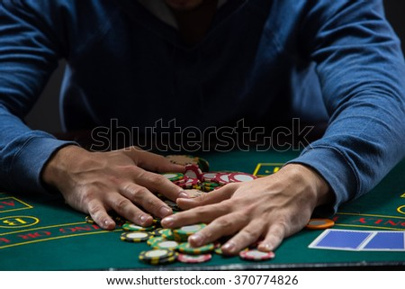 Poker player taking poker chips after winning - stock photo