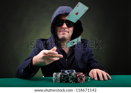 Poker player throwing two ace cards on black background - stock photo