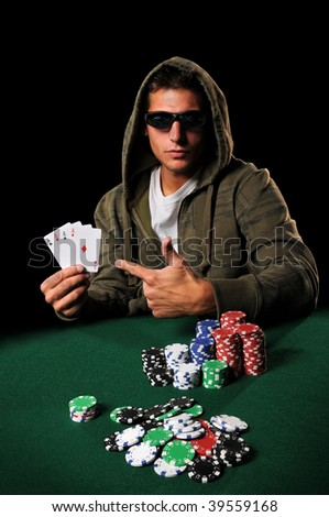 Poker player wearing sunglasses pointing to four aces over dark background