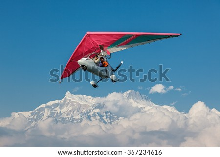 POKHARA, NEPAL - OCTOBER 30, 2009: The motor hang-gliding in the sky near the himalayan peaks Machhapuchre - Annapurna region, Nepal