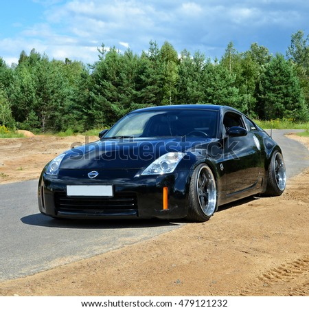 Poland - August 10, 2016: Beautiful elegant black car on the forest background. Autumn trip. Stylish modern vehicle. Nice weekend outdoors. Amazing landscape. Wonderful journey. In the woods