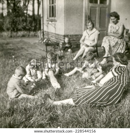 POLAND, CIRCA FORTIES: Vintage photo of women looking small children playing with rabbits outdoor