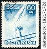 POLAND - CIRCA 1954: post stamp printed in Polska shows male athlete gymnast handstand on horizontal bars against blue sky from second summer spartacist games, Scott 629 A248 60g blue, circa 1954 - stock photo