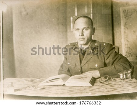 POLAND, FEBRUARY 27, 1946 - Vintage photo of man in uniform reading a book