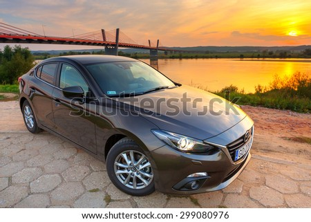 POLAND-SEPTEMBER 14, 2014: New Mazda 3 captured at sunset near Vistula river with HDR technique. Mazda 3 is a popular compact car manufactured in Japan by the Mazda Motor Corporation. - stock photo
