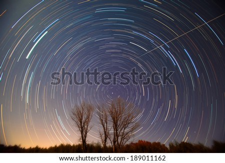 Polaris and star trails over the trees - stock photo