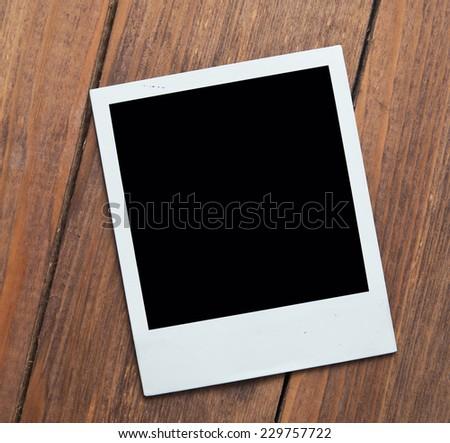 polaroid on wooden background - stock photo