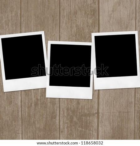 Polaroid photo frames on wooden background - stock photo