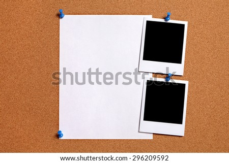 Polaroid photo prints, plain paper poster pinned to cork board.  Copy space.   - stock photo