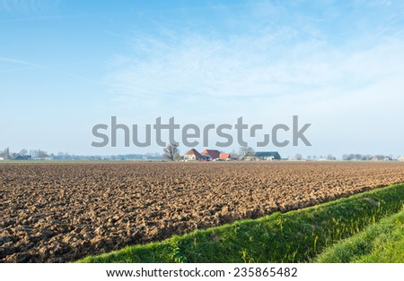 Polder in the Netherlands with a plowed field in the foreground and a colorful farm in the background. - stock photo