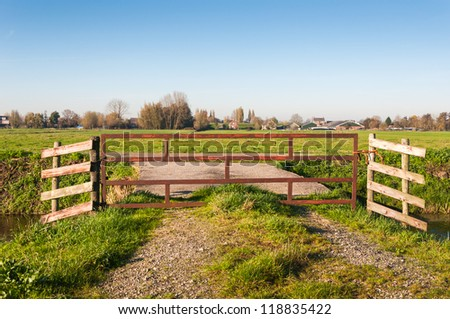 Polder landscape in the Netherlands with a small village in the background and a fence in the foreground. - stock photo