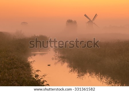 Polder landscape with Characteristic historic windmill on a foggy september morning in the Netherlands - stock photo