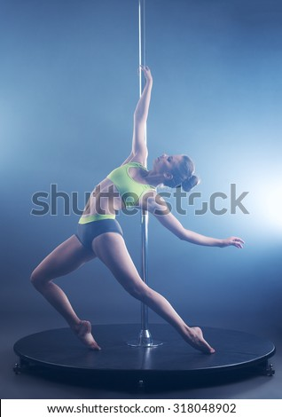 Pole dance. Sexy girl froze in graceful pose - stock photo