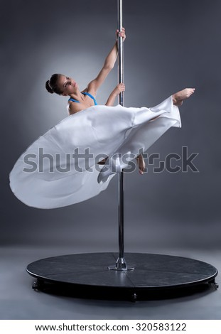 Pole dance. Sexy woman posing in elegant position