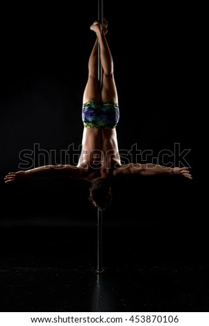 Pole dance. Shot of strong man hanging upside down
