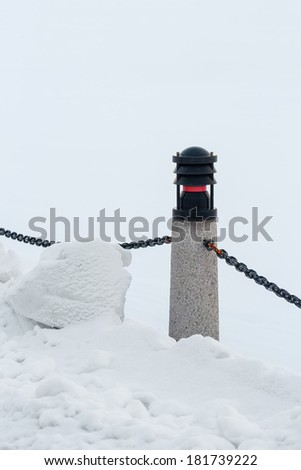 Pole with a chain in wintertime with snow piling up - stock photo