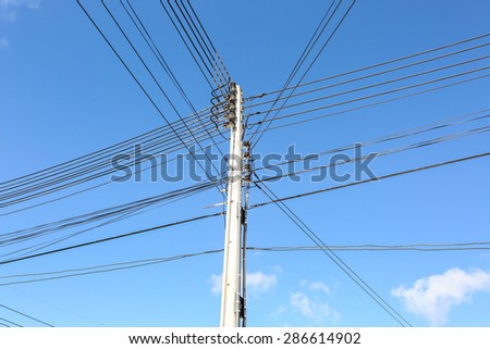 Pole with black cables and lines under blue sky