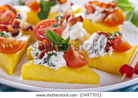 Polenta appetizers with herbed ricotta and bacon - stock photo