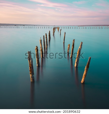 Poles in the water, on sunset clouds and ocean- calmness and silence concept - stock photo