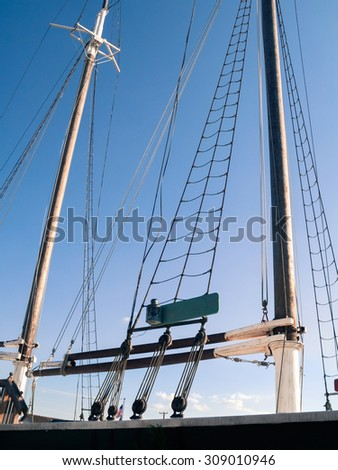 Poles, ropes and the rigging on a tall historic ship. - stock photo