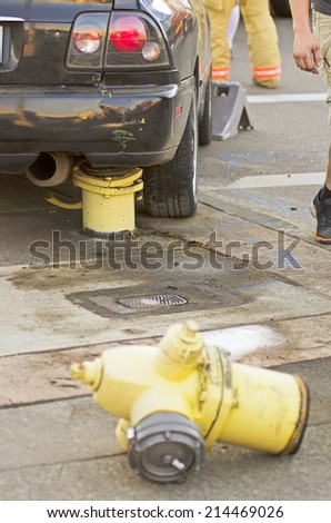 Police and fire equipment at the scene of a single car accident that knocked over a fire hydrant, - stock photo