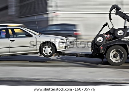 police department tow truck delivers the damaged vehicle - stock photo
