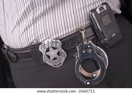 Police detectives belt with badge,cellphone and hadcuffs - stock photo
