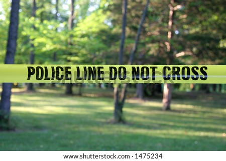 Police Do Not Cross – yellow plastic tape in a forest. - stock photo