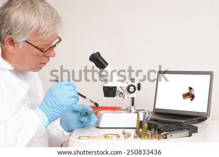 Police forensic technician in a laboratory, dusting a gun for finger prints and comparing spent bullets. - stock photo