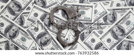 Police handcuffs lie on a lot of dollar bills. The concept of illegal possession of money, illegal transactions with US dollars. Economic Crime
