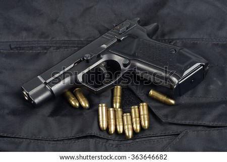 police handgun on black uniform background  - stock photo