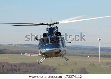 Police helicopter flies over the landscape - stock photo