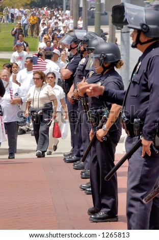 Police offers with batons stop demonstrators at illegal emigrant rally. May 1st 2006 - stock photo