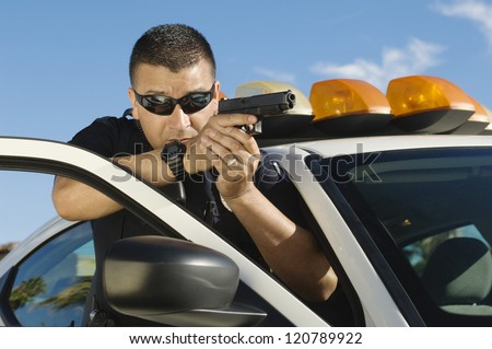 Police officer aiming with pistol by car - stock photo